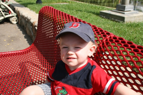 toddler on red bench baseball hat