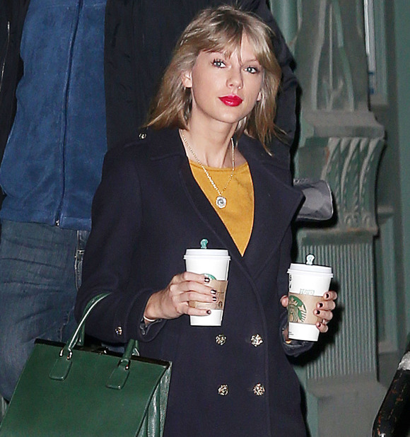Taylor Swift walks out of her apartment double-fisting two grande Starbucks coffees, wearing red pants and carrying a green purse on New Year's Day in NYC