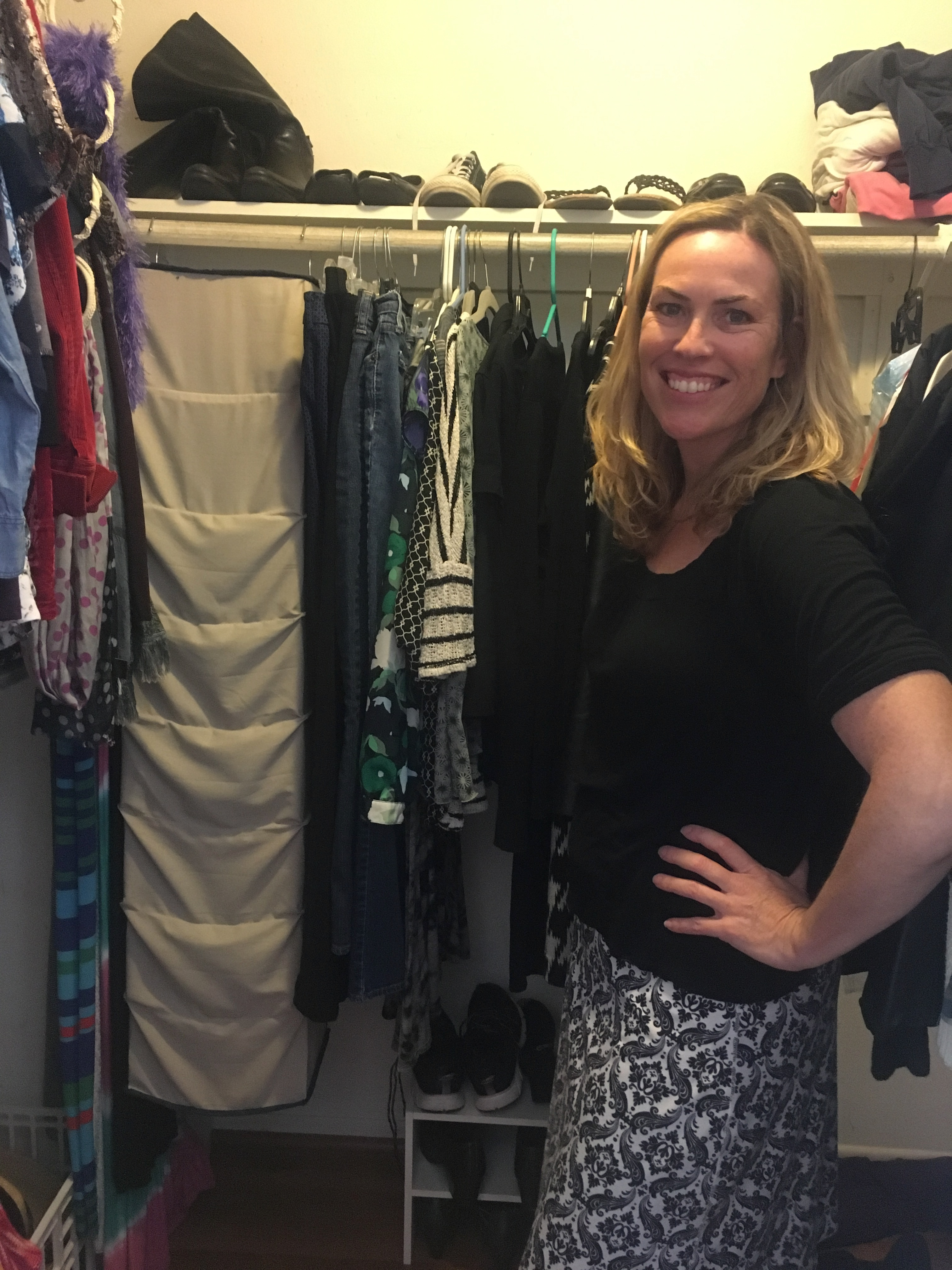 Woman next to her Project 333 wardrobe