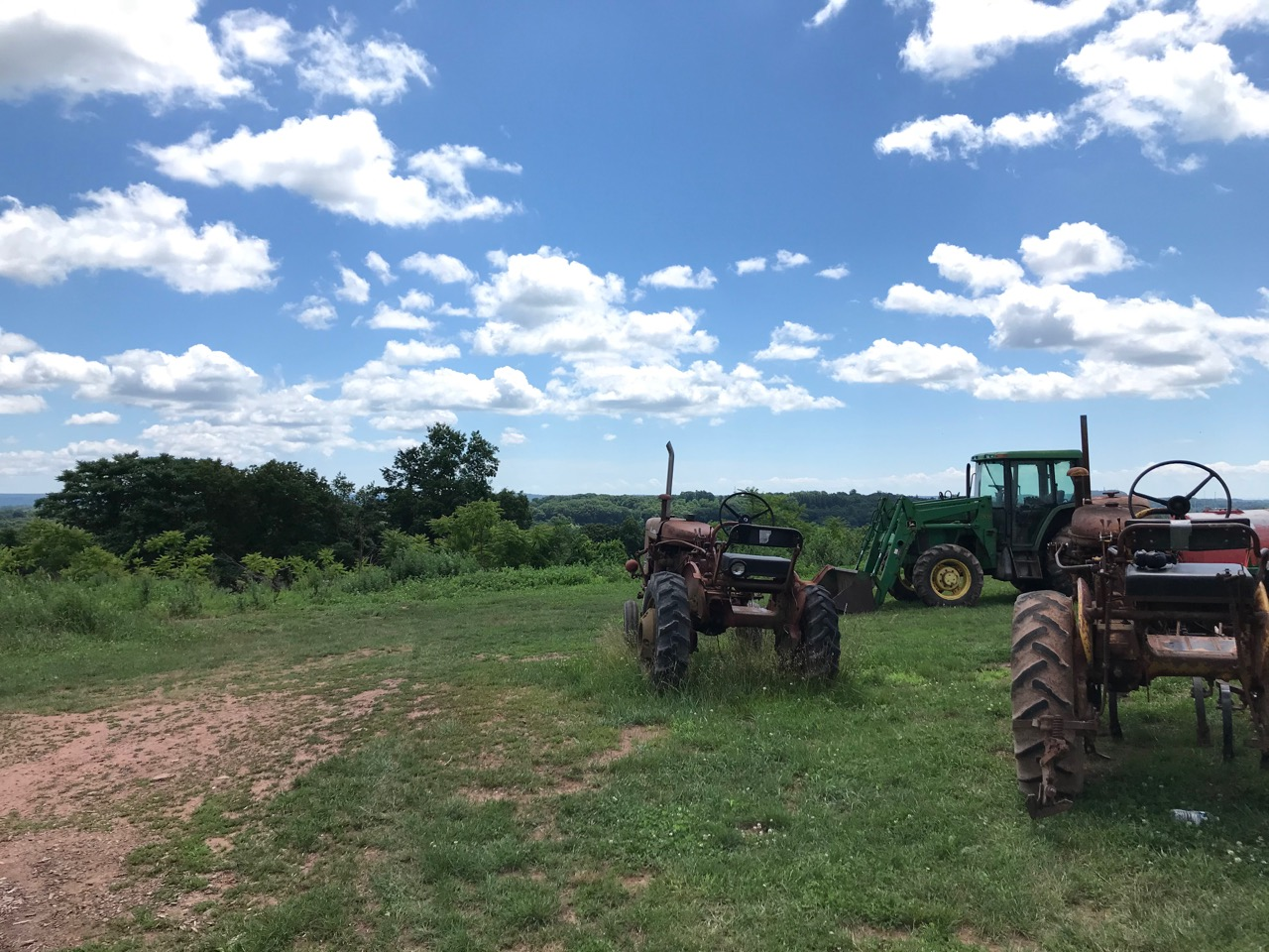 farm vehicles with blue sky and clouds in background